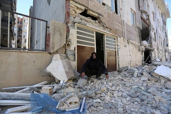 Homem é fotografado sentado sobre destroços (Crédito:  Tasnim News Agency/ Reuters))