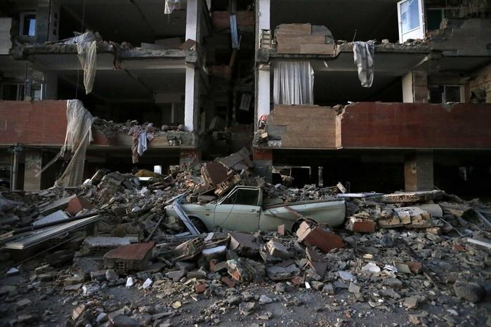 Carro destruído sob destroços (Crédito: Ouria Pakizeh/ISNA/AP)