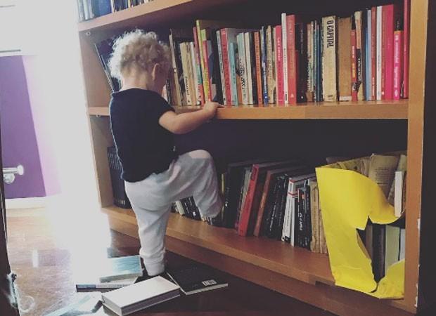 Madalena, filha de Pitty, brinca com estante de livros (Crédito: Reprodução)