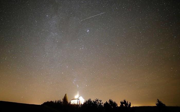 Um meteoro atravessa o céu sobre uma igreja ortodoxa em Zagorie, a 110 km a oeste da capital Minsk, na Bielorrússia  (Crédito: Sergei Grits / AP Photo)