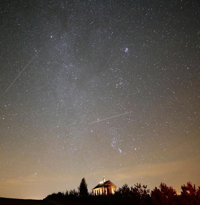 Céu iluminado durante chuva de meteoros da constelação de Gêmeos (Gemínideas) em Zagorie, na Bielorrússia, na noite de quarta-feira (13)  (Crédito:  Sergei Grits/ AP)