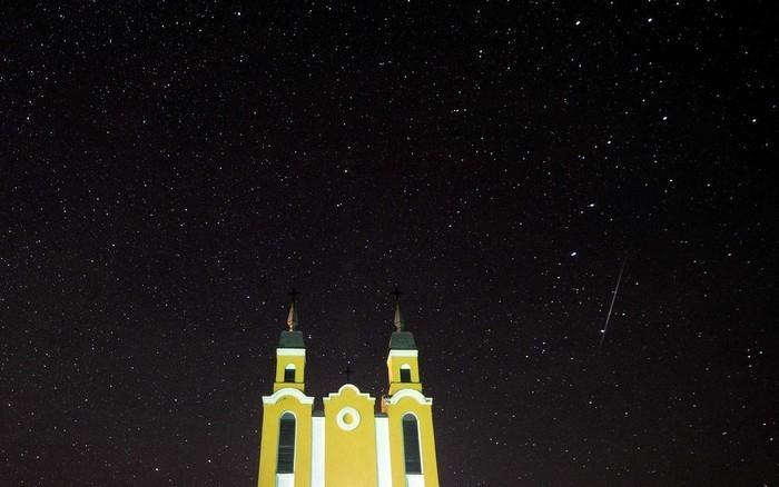 Meteoro no o céu atrás de uma igreja católica na vila de Krevo, a cerca de 100 km a noroeste de Minsk, na Biolorrússia  (Crédito: Sergei Gapon / AFP Photo)