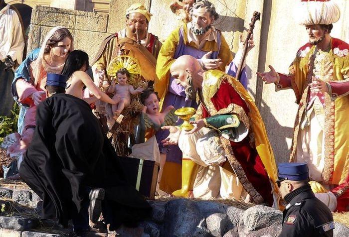 Ativista tenta pegar menino Jesus de presépio (Crédito: Reuters)