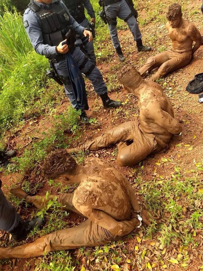 Homens foram encontrados imersos na lama tentando se esconder da polícia (Crédito: Reprodução)