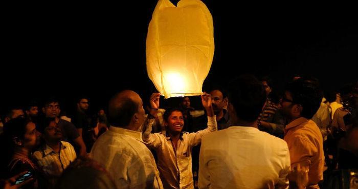 Indianos celebram a chegada de 2018 com uma lanterna em uma praia de Mumbai, na Índia