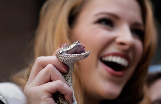 Miss Caroline Carothers posa sorridente ao segurar cobra cascavel
