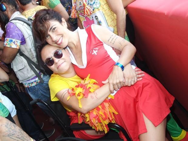 Maria Gadu de cadeira de rodas por que está com um problema nos ligamentos e a namorada Lua (Crédito: Reprodução)