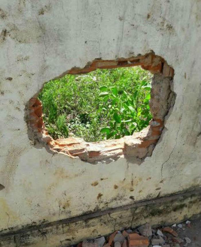 Buraco feito no muro para os detentos fugirem (Crédito: Reprodução)