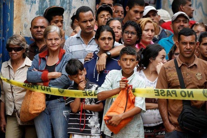 Moradores observam trabalho de investigadores em frente à padaria saqueada em Caracas (Crédito: Reprodução)