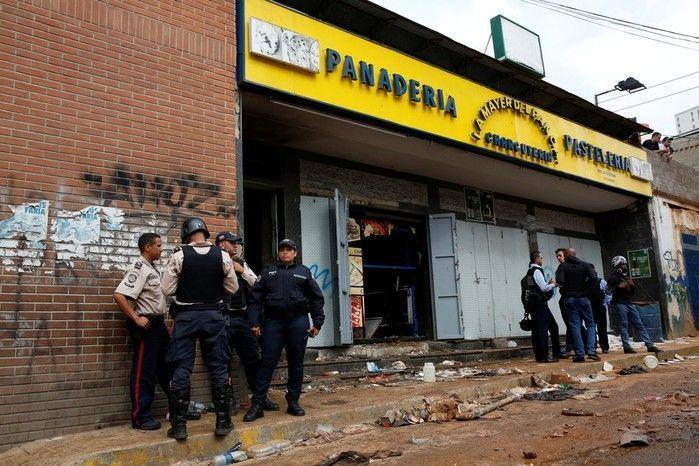 Policiais e investigadores em frente à padaria saqueada em Caracas (Crédito: Reprodução)