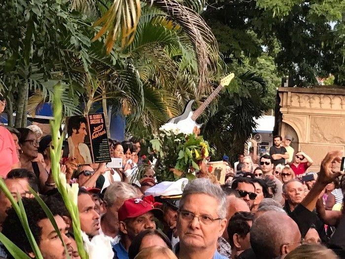 Vinis do cantor e uma guitarra podiam ser vistos durante o enterro (Crédito: G1)