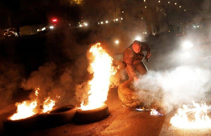 Policial tira pneu de barricada em chamas durante protesto na Rodovia Presidente Dutra, em São Paulo, no início da manhã desta sexta-feira (28) (Crédito: Reuters)