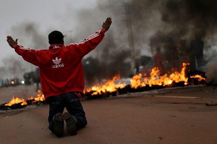 Membro do MTST se ajoelha diante de barricada em chamas em manifestação nesta manhã de sexta (28) em Brasília