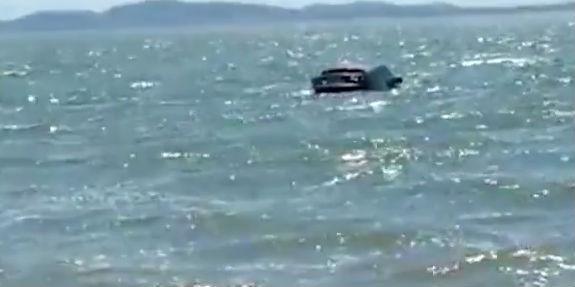 Carro de luxo roubado aparece boiando misteriosamente em lagoa