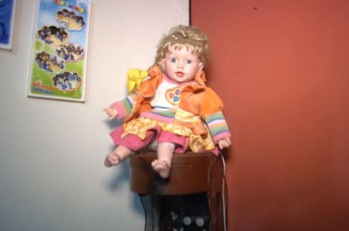 Boneca supostamente sai do canto onde deveria permanecer e também canta o Pai Nosso sem ninguém apertar o botão (Crédito: Reprodução)