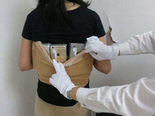 Mulher tenta viajar com 102 iPhones escondidos na roupa e é presa