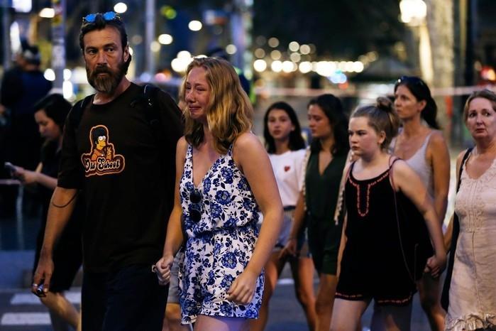 Mulher chora entre pedestres conduzidos pela polícia após ataque em Barcelona, na Espanha  (Crédito: Pau Barrena/AFP)