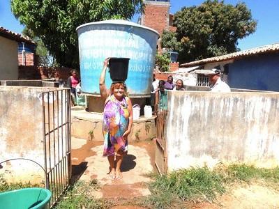 Essa senhora já de uma certa idade, com alguns problemas de saúde, tendo que se sacrificar com a lata d'água na cabeça (Crédito: Edinardo Pinto )