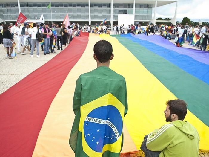 Manifestantes da 3ª Marcha Nacional contra a Homofobia ocupam a Praça dos Três Poderes e estendem uma bandeira, com as cores do movimento, em frente ao Palácio do Planalto (Crédito: Marcello Casal Jr/ABr)