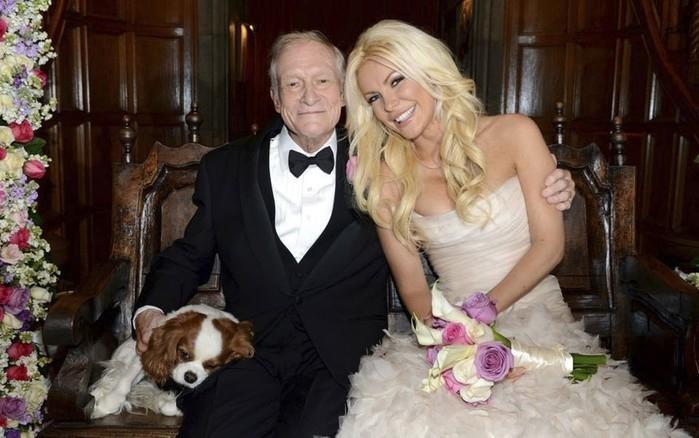 O fundador da 'Playboy', Hugh Hefner, posa com sua nova esposa, a coelhinha Crystal Harris, após o casamento celebrado na Mansão da Playboy, na Califórnia, no último dia de 2012. À esquerda, o cãozinho Charlie também aparece na foto (Crédito: Reuters)