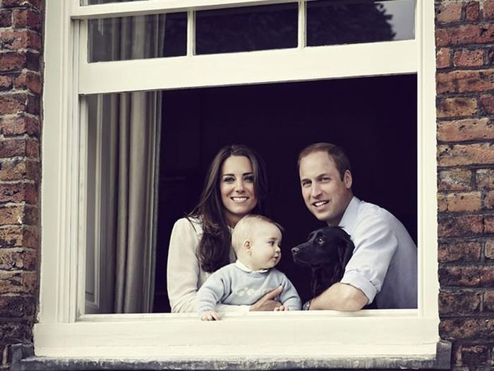 Em foto de 29 de março de 2014, o príncipe William, a princesa Kate, o filho George e o cachorro Lupo posam na janela do Palácio de Kensington, no Reino Unido  (Crédito: AFP)