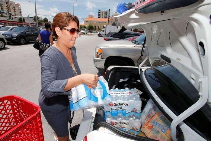 Americana carrega carro com água e suprimentos