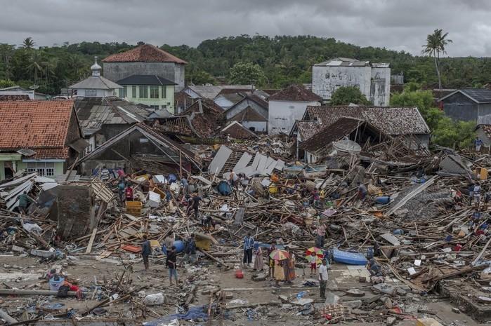 Pessoas inspecionam nesta segunda-feira (24) área destruída pelo tsunami em Sumur, na Indonésia (Crédito: Fauzy Chaniago/AP Photo )