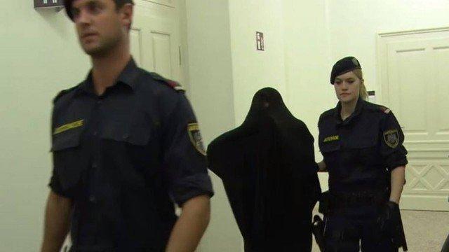 Com o rosto coberto, Silvia M. é conduzida por policiais em tribunal de Slazburgo (Crédito: Reprodução)