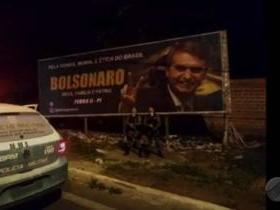 Policias em serviço posam em frente a outdoor de Bolsonaro no PI