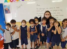 Para que aluno não se sinta diferente, colegas usam fitas no rosto