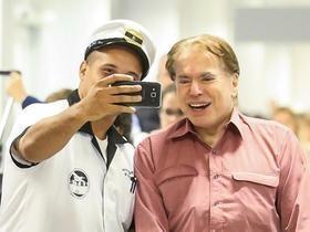 Silvio Santos volta ao Brasil e distribui selfies em aeroporto