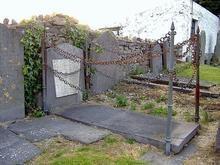 Saiba o por que esta sepultura fica rodeada por estacas e correntes