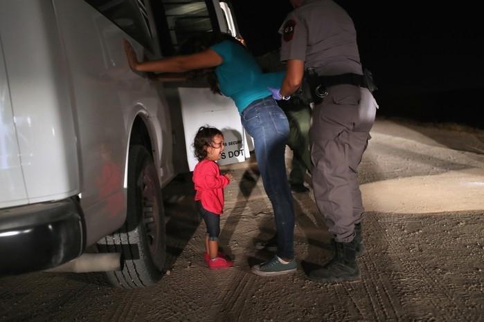 Criança de dois anos chora ao sua mãe ser revistada e detida em McAllen, nos EUA (Crédito: JOHN MOORE / GETTY IMAGES NORTH AMERICA / AFP)