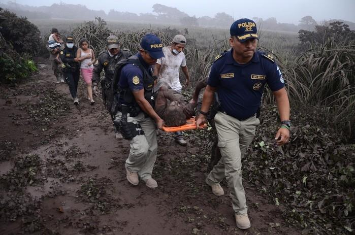 Policiais carregam ferido na erupção do Vulcão do Fogo, em El Rodeo, no departamento de Escuintla, no domingo (3)  (Crédito: Noe Perez / AFP)