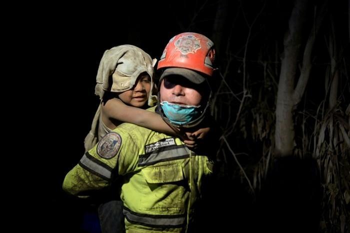 Criança coberta de cinzas é socorrida em El Rodeo, após a erupção de vulcão de Fogo, na Guatemala, no domingo (3)  (Crédito: Fabricio Alonzo/ Reuters)