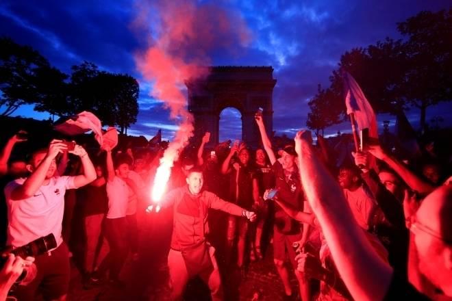 Torcedores em frente ao Arco do Triunfo, comemorando vitória da França (Crédito: Gonzalo Fuentes/Reuters)