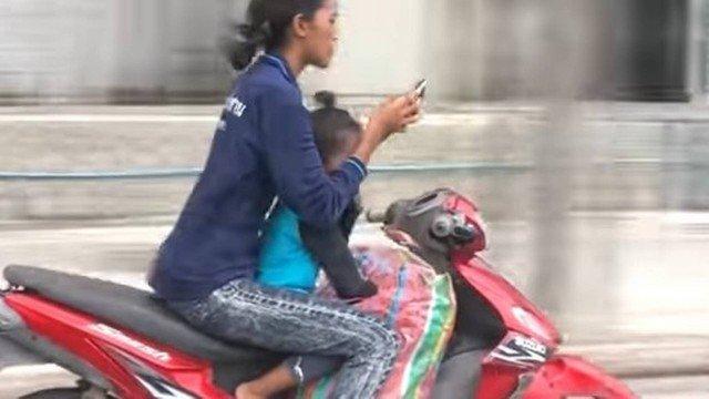 Mulher tira as mãos do guidão ao usar smartphone sobre moto  (Crédito: Reprodução/YouTube)