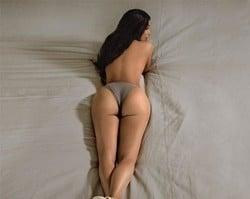 De topless, Kim Kardashian mostra o famoso bumbum deitada na cama