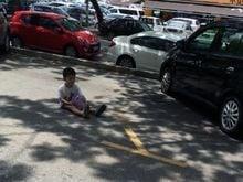 Mãe deixa filho sentado na rua para guardar vaga de estacionamento