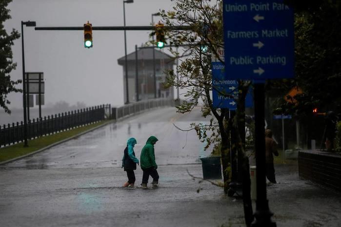 Moradores andam em rua local enquanto as águas do rio Neuse começam a transbordar e alagar casas durante a chegada de Florence à cidade de New Bern, na Carolina do Norte, nesta quinta (Crédito: Eduardo Muñoz/Reuters)