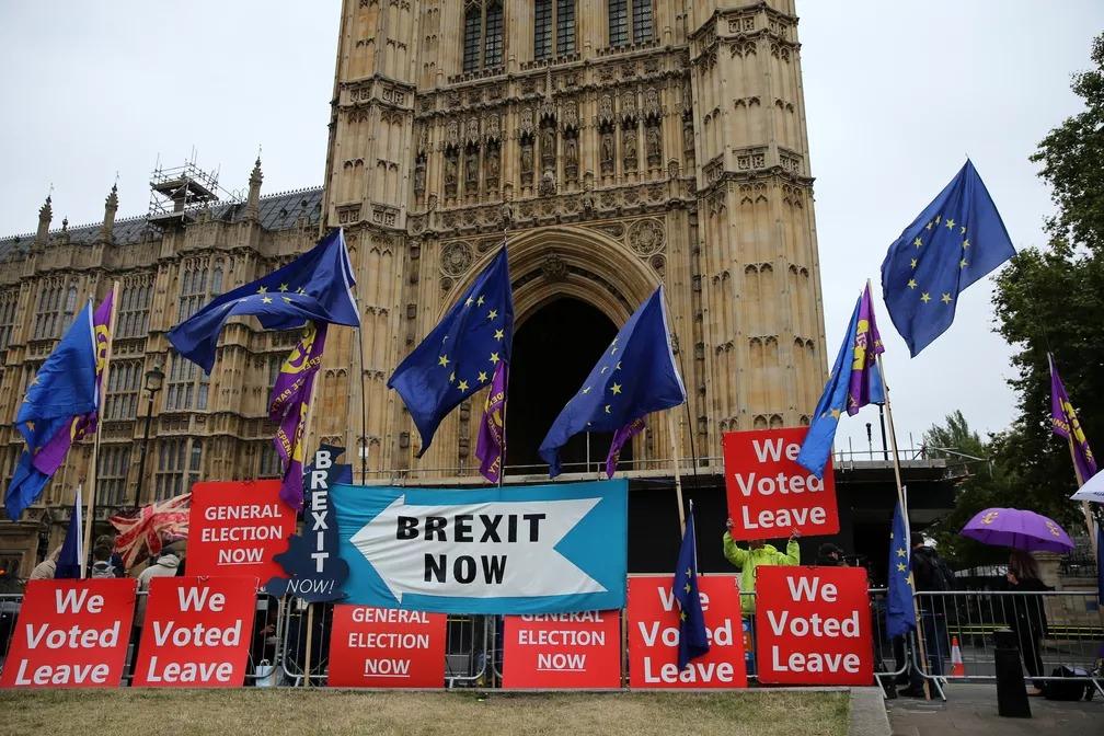 """Manifestantes pró-Brexit seguram cartazes que dizem """"Brexit agora"""" e """"nós votamos para sair [da União Europeia]"""" do lado de fora do Parlamento britânico em Londres nesta segunda-feira (9). — Foto: Isabel Infantes/AFP"""