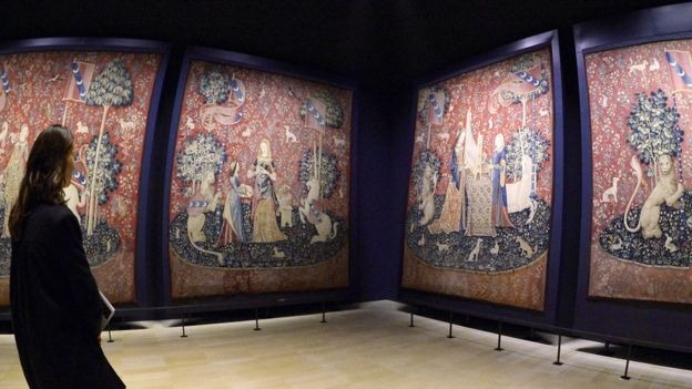 Mulher vendo peças da série de tapeçaria 'A dama e o unicórnio' expostas em galeria