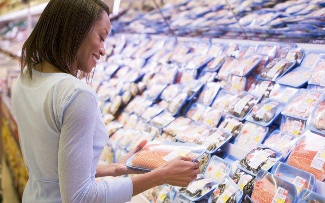 Mulher escolhendo um peixe no mercado