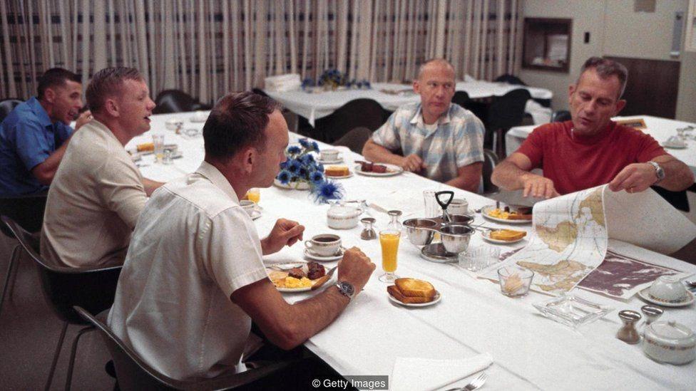 Tripulação da Apollo 11 sentada à mesa, antes de lançamento