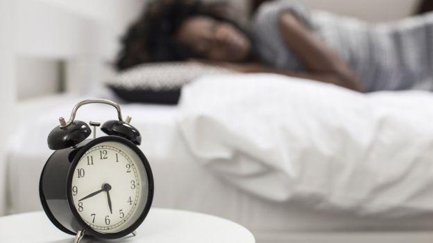 Foto mostra relógio em destaque, com mulher dormindo na cama no plano de fundo