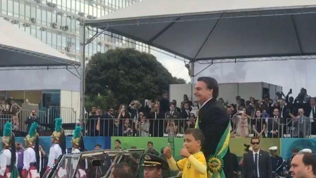 Presidente e o filho repetiram cena da posse e saudaram o público juntos no desfile no Rolls Royce da Presidência. Primeira-dama Michelle Bolsonaro e os filhos Flávio e Eduardo Bolsonaro estão no palanque presidencial