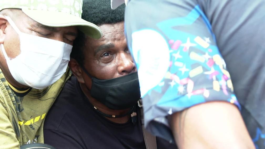 Neguinho da Beija-Flor é amparado por amigos no enterro do neto - Foto: TV Globo
