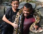 Pai e filho nadam com enorme píton impressionam na internet; vídeo