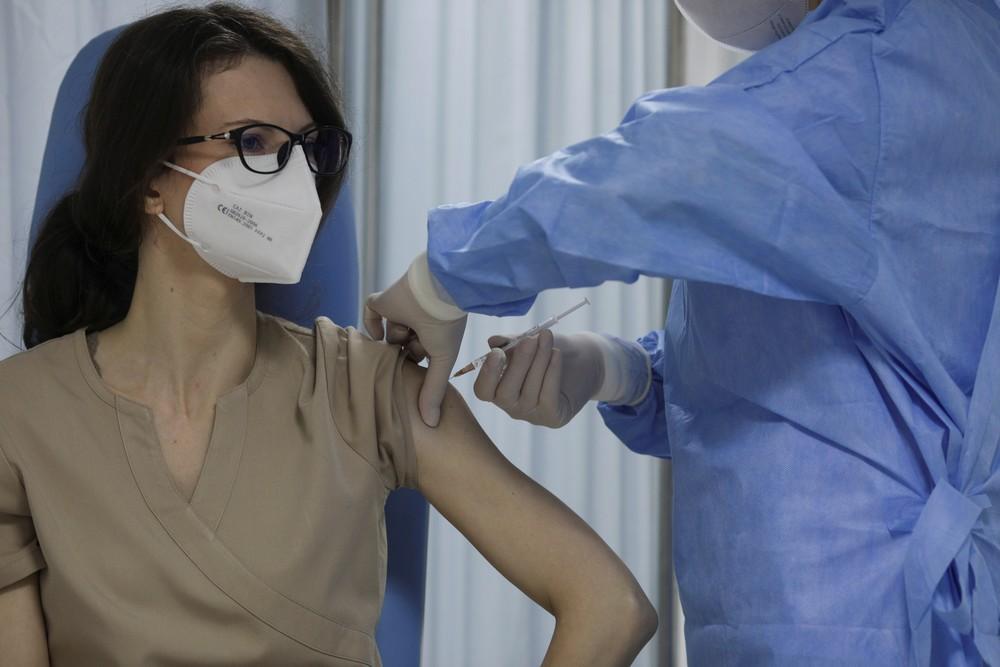 Uma enfermeira romena recebe vacina contra a Covid-19 — Foto: Octav Ganea/Reuters