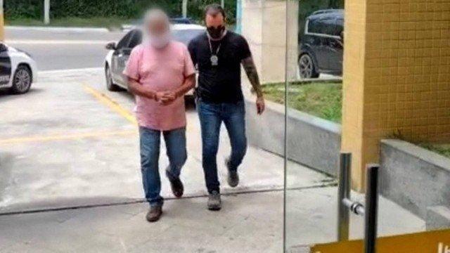 O acusado é conduzido por um policial civil na entrada da 132ª DP, em Arraial do Cabo Foto: Divulgação